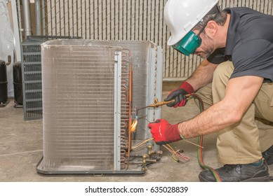 HVAC technician soldering a copper joint on a condensing coil wearing safety gear.