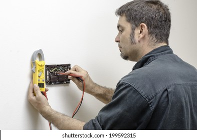 HVAC technician testing voltage on a mercury thermostat.