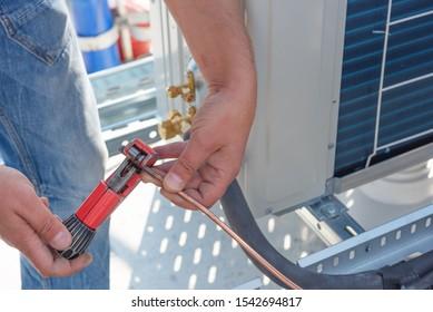 Der HVAC-Techniker arbeitet an Klimaanlagen auf dem Dach des neuen Industriegebäudes. Der Techniker installiert die Klimaanlage.Schneiden der Kupferleitung mit Rohrschneider.