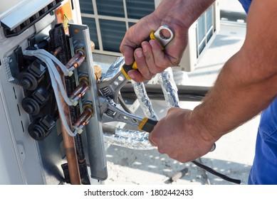 Der HVAC-Techniker arbeitet an Klimaanlagen auf dem Dach des neuen Industriegebäudes. Der Techniker benutzt einen Fixschlüssel, um die Außenlufteinheit zu straffen. Der Mensch hält einen Schlüssel in der Hand.