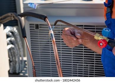 Der HVAC-Techniker arbeitet an Klimaanlagen auf dem Dach des neuen Industriegebäudes. gepfropftes Bild des HVAC-Technikers, der die Verbindung von Kupfer-Rohr-Klimaanlage schweißt.