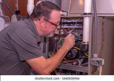 HVAC Technician Working On A High Efficiency Gas Furnace  Gray Shirt