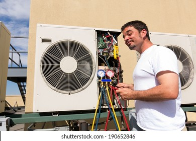 HVAC technician working on a mini-split condensing rooftop unit.