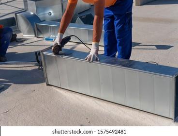 Der HVAC-Techniker arbeitet an einem Dach des neuen Industriegebäudes. Nahaufnahme des jungen Technikers, der einen Luftkanal mit dem Winkelschleifer repariert. HVAC-Arbeiter Schneidedraht mit Winkelschleifer.
