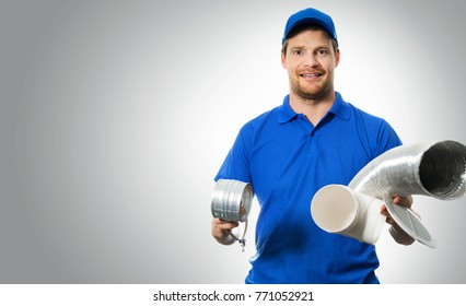 hvac worker with ventilation system equipment in hands on gray background