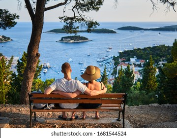 HVAR, CROATIA-JULY 3, 2019: A couple in love enjoying the beauty of nature sitting on a bench on a pleasant evening.