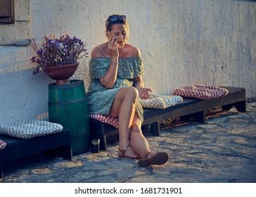 HVAR ISLAND, CROATIA, JULY 3, 2019: A Lady Engrossed in deep conversation while having a smoke.