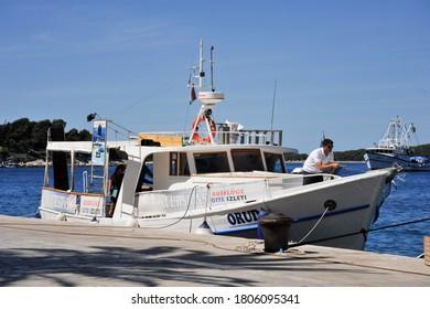 HVAR PORT, HVAR / CROATIA - JUNE 14 2012: A deckhand hoses down the deck of excursion tour boat docked at the quay, at Hvar harbor, on the island of Hvar.