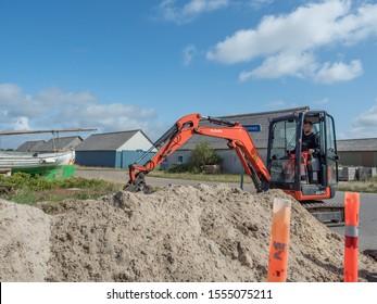 Hvide Sande Jutland August 12th 2019 - Kubota Orange Excavator digging at a road work site in a sunny summer afternoon