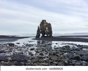 Hvitserkur, dinosaur of Iceland, the troll rock formation look like dragon drinking, the basalt sea stack off shore during low tide on black sand, mud and gravel in foreground on bright sky.