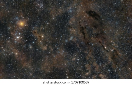 Hyades star cluster with bright orange star Aldebaran and space dust between stars in Constellation Taurus. Faint dust lanes in deep space long exposure.