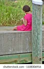 Hyannis, Massachusetts/USA- July 27, 2013: A vertical image of an unidentified young woman in a pink dress, sitting on a pier on a summer afternoon.