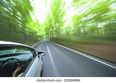 A Hybrid Car Running In Fresh Green