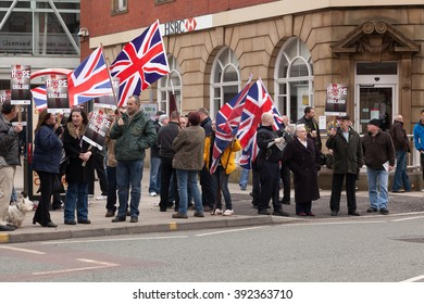 HYDE, LANCASHIRE, ENGLAND UK - FEBRUARY 25, 2012: Protesters from the British National Party gathered on the street during an English Defence League march. They are carrying flags and placards.