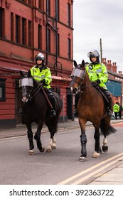 HYDE, LANCASHIRE, ENGLAND, UK - FEBRUARY 25, 2012: Two mounted police officers during an English Defence League march.  The officers and horses are wearing protective gear and are armed with batons.