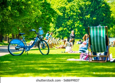 Hyde park in London during warm sunny day. People sitting on the grass having lunches. Amazing summer or spring spirit in UK. Barclays bicycle.