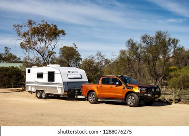 HYDEN, WESTERN AUSTRALIA - JULY 1, 2018: Ford Ranger Wildtrack off road pickup car with air intakes and a white caravan trailer in Western Australia prepared for an adventure.