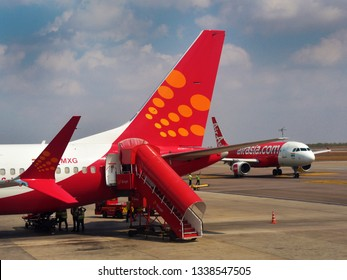 HYDERABAD, ANDHRA PRADESH, INDIA, MARCH 02, 2019: Tail end of a SpiceJet airline with ladder in the foreground, and an AirAsia jet in the background, on the tarmac on a sunny day.