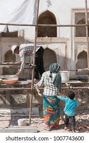 Hyderabad / India 26 December2017  Masonry Man Working with woman labour On A Golkonda or Golconda fort old Wall  at Hyderabad Telangana India