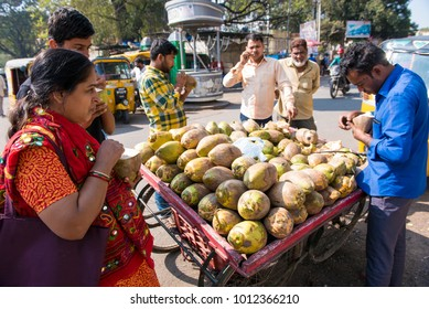 Hyderabad / India 30 December2017 woman holding fresh coconut water standing near Coconut cart at Nampally in Hyderabad Telangana India