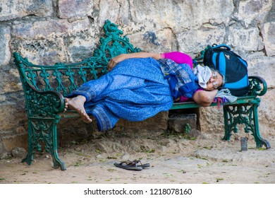 Hyderabad / India - Dec 2017: The old Indian lady is resting on metal bench in the Golconda fort. Best destination in IncredibIe India.