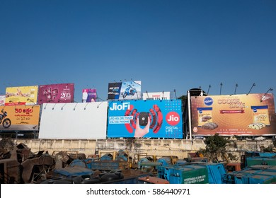 HYDERABAD, INDIA - FEBRUARY 21,2017 Hoarding and billboards dot the sky advertisements of various companies near a garbage truck dump yard in Hyderabad,India