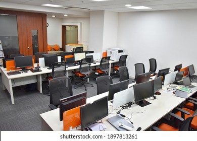 Hyderabad, India - January 19, 2021: Side view of white and orange open space office interior with rows of computer tables with desktops standing on them