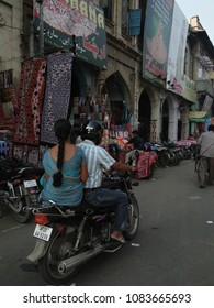 HYDERABAD, INDIA -  NOV 21, 2009 - Women in sarees ride sidesaddle as motorbikes weave their way through traffic in the Charminar bazaar district India, Asia