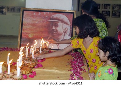 HYDERABAD, PAKISTAN - APR 03: Children lighten candles in front of portrait of Zulfiqar Ali Bhutto Founder of Peoples Party (PPP) on April 03, 2011in Hyderabad, Pakistan.