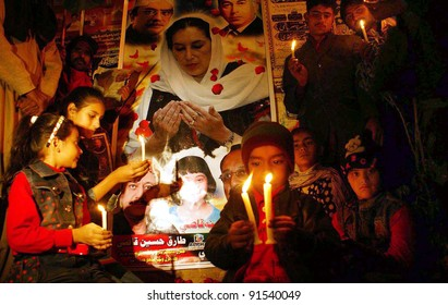 HYDERABAD, PAKISTAN - DEC 26:unidentified Supporters of Peoples Party (PPP) lighten candles during a ceremony to mark the fourth death anniversary of Benazir Bhutto at Hyderabad press club on December 26, 2011.
