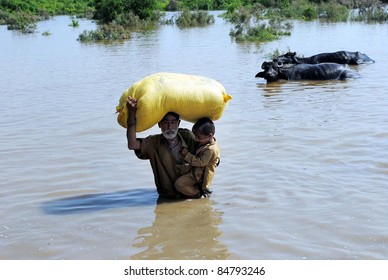 HYDERABAD, PAKISTAN - SEPT 16: An aged rain affected man holds a child and bag over his head passes through a flooded area as he is moving towards safe place after his house was inundated with rainwater September 16,2011, Hyderabad