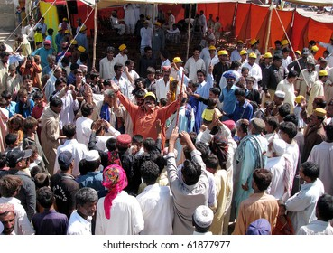 HYDERABAD, PAKISTAN-SEPT 26: Internally displaced people dance during mass wedding ceremony of their relatives held at flood affectees relief camp established at Sabzi Mandi Sept 26, 2010 in Hyderabad