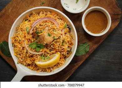 Hyderabadi Chicken Biryani served with Yogurt raita and Salan, Top down view