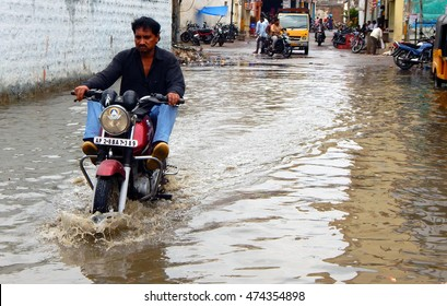 HYDERABAD,INDIA-AUGUST 25:Motor cyclist ride in rain water flooded road  in sudden downpour showing problematic road and drainage situation and people suffering on August 25,2016 inHyderabad, India