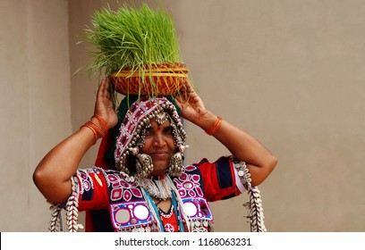 HYDERABAD,INDIA-AUGUST 29: Indian tribal lambadi woman dance with germinated wheat grass in bamboo basket in Kajal Teej Monsoon Festival on August 29,2018 in Hyderabad