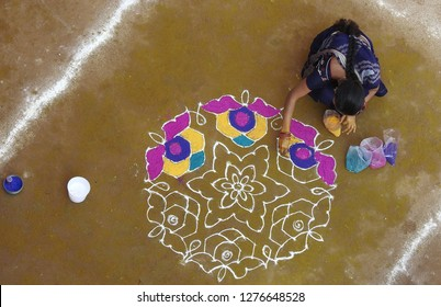 HYDERABAD,INDIA-DECEMBER 6: woman draw rangoli with dots and pattern,decorate with colorful powders,during pongal or makara sankranti,tradition in all occasions  on December 6,2019 in Hyderabad