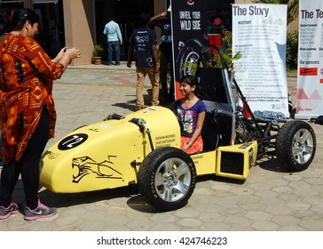 HYDERABAD,INDIA-FEBRUARY 22:Indian Mother take photo with mobile phone child play with race car model in the automobile exhibition on February 22,2015.