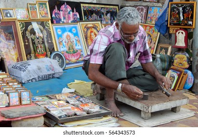 HYDERABAD,INDIA-JANUARY 25:Indian man work on photo frames outdoors on foot path of busy road, common scene for gods photos,on January 25,2017 in Hyderabad,India