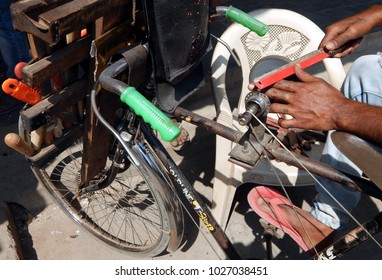 HYDERABAD,INDIA-JANUARY 26:Man sharpens knife with bicycle powered stone wheel on the street on January 26,2018 in Hyderabad