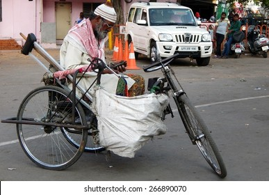 HYDERABAD,INDIA-MARCH 17: Indian physically challenged seek help sitting on a tricycle in a busy road on  March 17,2015 in Hyderabad,India.common scene in India.