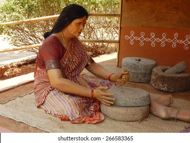 HYDERABAD,INDIA-MARCH 28:Rural Indian woman figure using stone grinder to  grinding grain with a hand mill to make flour in Shilparamam on March 28,2015 in Hyderabad,India.