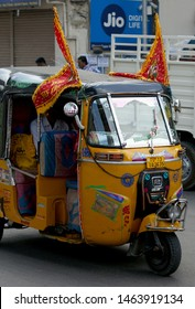 HYDERABAD,INDIA-MARCH 31:Indian people take Hindu God Hanuman in auto rickshaw with safrfron flags tied to it ,in Shoba yatra or procession on Hanuman jayanti festival, on March 31,2018 in Hydeabad