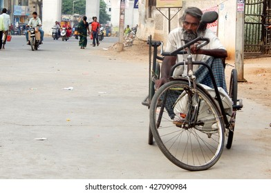 HYDERABAD,INDIA-MARCH 3:Physically challenged senior Indian,using tricycle, seeking help,beg, or seek alms in busy road  on March 3 ,2016