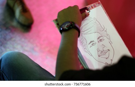 HYDERABAD,INDIA-OCTOBER 14:Closeup photo of an artist drawing caricature of a visitor  in Hyderabad Comic Con 2017 on October 14,2017 in Hyderabad,India