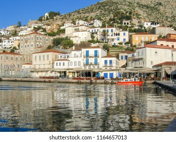 Hydra Greece )1/03/2005: reflection in waters of harbour with red boats and town in background