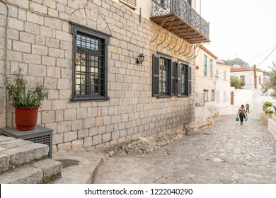 Hydra Island, Greece - October 17, 2018: A young woman returns home from running errands, walking along beautiful cobblestone back streets on the enchanting, Greek Island of Hydra.