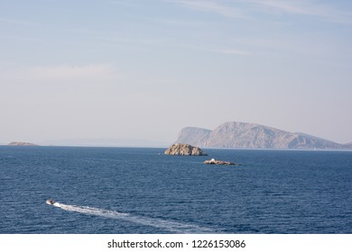 Hydra Island, Greece - October 17, 2018: A small, rocky island juts out of a beautiful blue sea, in the Aegean Sea, near the Greek Island of Hydra.