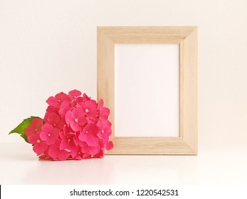 Hydrangea flower and blank photo frame on table in front of the wall