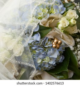 hydrangea, roses, Gypsophila baby's breath wedding day bouquet flowers partially covered by veil.