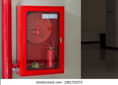 Hydrant with water hoses and fire extinguish equipment. Fire safety equipment in the red box on wall cement . Hydrant with water hoses and fire extinguish equipment / fire hose box .